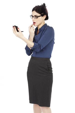 early 30s: An adult (early 30s) black haired caucasian woman wearing a blue buttoned shirt and a dark gray skirt,looking at a small makeup mirror shes holding in her hand, and applyinig lipstick on her lips. Isolated on white background. Stock Photo