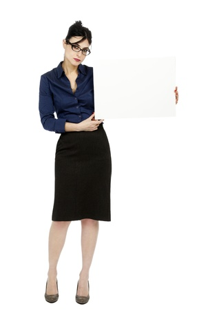early 30s: An adult (early 30s) black haired caucasian woman wearing a blue buttoned shirt and a dark gray skirt, holding a blank sign next to her while looking at the camera serious expression. Isolated on white background.
