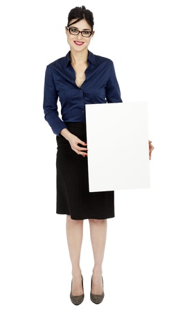 early 30s: An adult (early 30s) black haired caucasian woman wearing a blue buttoned shirt and a dark gray skirt, holding a blank sign in front of her while looking at the camera with a large toothy smile. Isolated on white background.