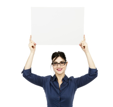early 30s: An adult (early 30s) black haired caucasian woman wearing a blue buttoned shirt and a dark gray skirt, holding a blank sign over her head while looking at the camera with a large toothy smile. Isolated on white background.