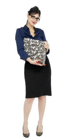 early 30s: An adult (early 30s) black haired caucasian woman wearing a blue buttoned shirt and a dark gray skirt, holding a ring binder folder and a pen while looking at the with a lovely smile. Isolated on white background.