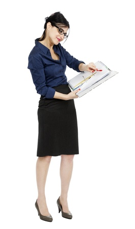 early 30s: An adult (early 30s) black haired caucasian woman wearing a blue buttoned shirt and, a dark gray skirt and a big toothless smile; holding a ring binder folder and pointing with her pen to a certain detail in the document. Isolated on white background.