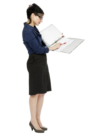 An adult (early 30's) black haired caucasian woman wearing a blue buttoned shirt and and a dark gray skirt, holding a ring binder folder and pointing with her pen to a certain detail in the document. Isolated on white background.
