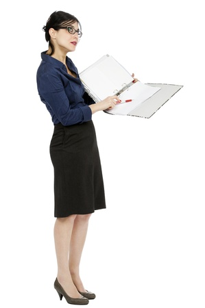 early 30s: An adult (early 30s) black haired caucasian woman wearing a blue buttoned shirt and and a dark gray; holding a ring binder folder and pointing with her pen to a certain detail in the document while glancing up, as if contemplating the subject. Isolated o Stock Photo