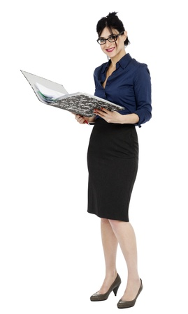 early 30s: An adult (early 30s) black haired caucasian woman wearing a blue buttoned shirt and a dark gray skirt, holding a ring binder folder and a pen; shes looking at the camera with a large toothy smile. Isolated on white background.  Stock Photo