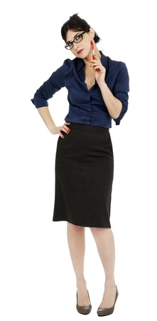 An adult (early 30s) black haired caucasian woman, wearing a blue buttoned shirt and a dark gray skirt, glancing up and plays with her pen while her other hand is on her hip. Seems shes processing a thought. Isolated on white background. photo