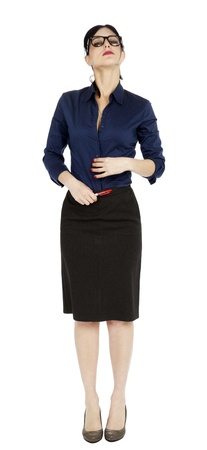 early 30s: An adult (early 30s) black haired caucasian woman, wearing a blue buttoned shirt and a dark gray skirt, glancing at the camera from above, as her neck jis stretched and her chin lifted. Seems shes processing a thought. Isolated on white background.