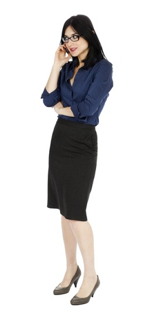 early 30s: An adult (early 30s) black haired caucasian woman, wearing a blue buttoned shirt and a dark gray skirt, seems to be very intereseted in what shes hearing for the other party in her phone conversation. Isolated on white background. Stock Photo