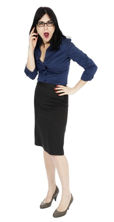 early 30s: An adult (early 30s) black haired caucasian woman, wearing a blue buttoned shirt and a dark gray skirt, and her awed expression suggests she is completely in shock by what shes hearing from the other party in her phone conversation. Isolated on white ba