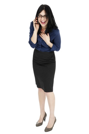 early 30s: An adult (early 30s) black haired caucasian woman, wearing a blue buttoned shirt and a dark gray skirt; her head tilted down, eyes closed and she is laughing her heart out on the phone. Isolated on white background.