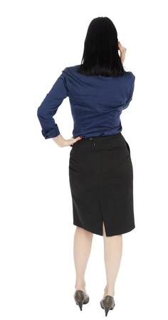 listening back: An adult (early 30s) black haired caucasian woman, wearing a blue buttoned blouse and a dark gray skirt; standing with her back to the camera while talking on the phone. Isolated on white background. Stock Photo