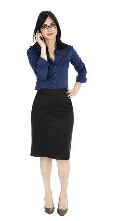 early 30s: An adult (early 30s) black haired caucasian woman, wearing a blue buttoned shirt and a dark gray skirt; looking at the camera while listening on the phone. Isolated on white background. Stock Photo