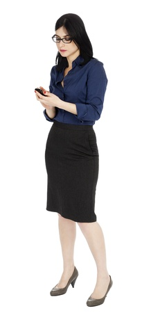 early 30s: An adult (early 30s) black haired caucasian woman, wearing a blue buttoned shirt and a dark gray skirt looking at a cellular phone - perhaps reading a message or dialing. Isolated on white background. Stock Photo