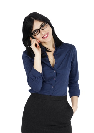 An adult (early 30s) black haired caucasian woman, wearing a blue buttoned shirt and a dark gray skirt; looking at the camera with a large toothy smile while on the phone. Isolated on white background. photo