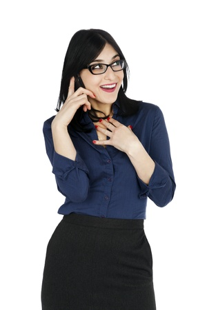 An adult (early 30s) black haired caucasian woman, wearing a blue buttoned shirt and a dark gray skirt; looking upwards while talking on the phone in a joyful manner. Isolated on white background. photo
