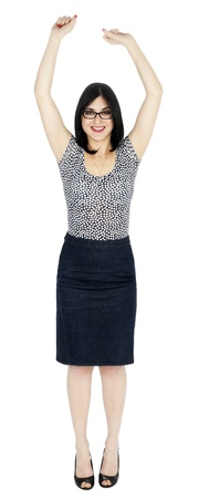 early 30s: An adult (early 30s) black haired caucasian woman, wearing a dotted shirt and a dark jeans skirt  looking at the camera with a large toothy smile while raising her arms up high. She is very satisfied by success. Isolated on white background. Stock Photo
