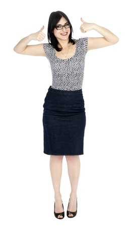 An adult (early 30s) black haired caucasian woman, wearing a dotted shirt and a dark jeans skirt looking at the camera with a toothy smile and her arms raised in thumbs up motion. She is very satisfied. Isolated on white background. photo