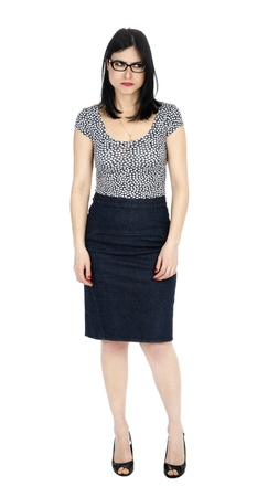 early 30s: An adult (early 30s) black haired caucasian woman, wearing a dotted shirt and a dark jeans skirt, glancing to her left with a childlike frowny expression and posture. Isolated on white background.