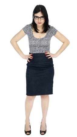 An adult (early 30s) black haired caucasian woman, wearing a dotted shirt and a dark jeans skirt, standing in an aggressive posture with her hands on her hips, and an angry expression on her face. Isolated on white background. photo