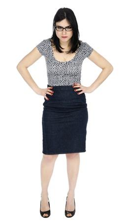 Un adulte (début des années 30) noir femme de race blanche aux cheveux longs, vêtu d'une chemise en pointillés et une jupe en jeans noir, debout dans une posture agressive avec ses mains sur ses hanches, et une expression de colère sur son visage. Isolé sur fond blanc.