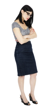 early 30s: An adult (early 30s) black haired caucasian woman, wearing a dotted shirt and a dark jeans skirt  looking down with a somewhat melancholic expression and posture. Isolated on white background. Stock Photo