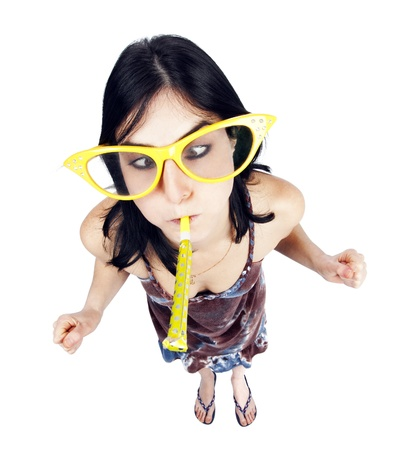 exaggerate: High and very wide angle full length view of an adult Caucasian black haired woman in her early 30s, wearing funky oversized spectacles and blowing a party horn blower while making a face with her eyes crossed. Isolated on white background. Stock Photo
