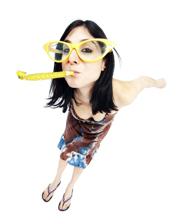 High and very wide angle full length view of an adult Caucasian black haired woman in her early 30's, wearing funky oversized spectacles and blowing a party horn blower while looking at the camera with a playful gaze. Isolated on white background.