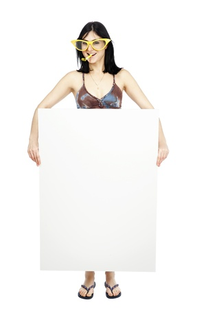 early 30s: Full length view of an adult Caucasian black haired woman in her early 30s, wearing funky oversized spectacles and a party horn blower in her mouth, holding a blank sign. Isolated on white background.