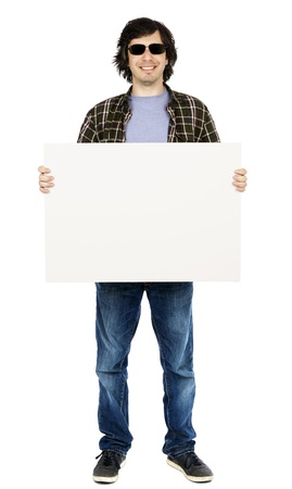 apparently: Caucasian male in his early 30s dressed in a casual attire and holding a large blank white sign, apparently looking at the camera through his sunglasses with a toothy smile. Isolated on white background.