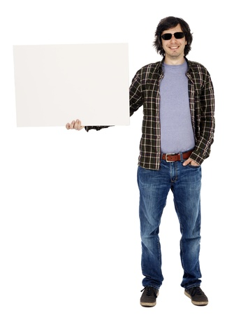 apparently: Caucasian male in his early 30s dressed in a casual attire and holding a blank white sign with one hand, apparently looking at the camera through his sunglasses with a toothy smile. Isolated on white background.