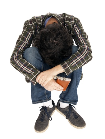 hip flask: A caucasian male in his early 30s dressed in a casual attire, sitting on the floor, head hidden between his knees and holding an open hip flask. He must have drunk himself unconscious, or just having a bad trip. Isolated on white background.