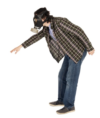 A caucasian male in his early 30s dressed in a casual attire and wearing a gas mask, trying to reach something, leaning towards it. Isolated on white background. photo