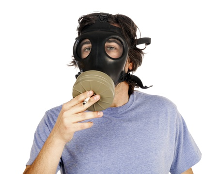 early 30s: Head and shoulders view of an adult (early 30s) Caucasian man wearing a gas mask and smoking a cigarette through the filter. Isolated on white background. Stock Photo