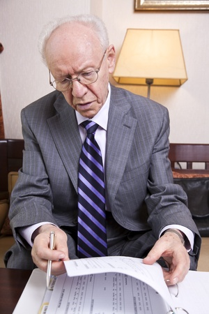 adult 80s: An elderly (in his 80s) business man wearing suit and tie sitting in a hotels business lounge, going over some papers.