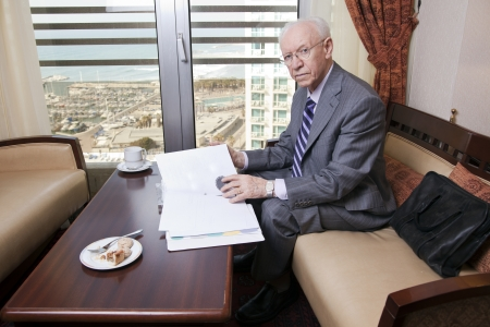 An elderly (in his 80s) business man wearing suit and tie sitting in a hotels business lounge, looking at camera, as if disturbed in the middle of going over some papers after having coffee. The sea and a marina can be seen defocused in the background. photo