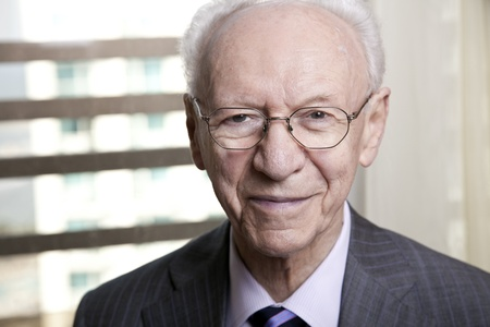 real people: Close-up portrait of a senior businessman (in his 80s) smiling to the camera wearing a suit and tie, as well as old fashion glasses.