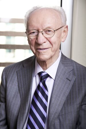 Medium close-up portrait of a senior businessman (in his 80s) smiling to the camera wearing a suit and tie, as well as old fashion glasses. Stock Photo
