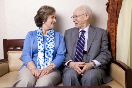 late 60s: A high society senior couple (hes in his 80s, shes in her late 60s) sitting on a sofa looking at eachother with very much love and joy.