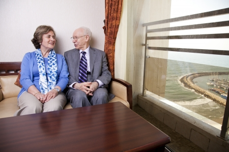 A high society senior couple (hes in his 80s, shes in her late 60s) sitting on a sofa, looking very much in love. The man is looking at the woman as she is glancing at the window, out of which the seashore and a marina can be seen. photo