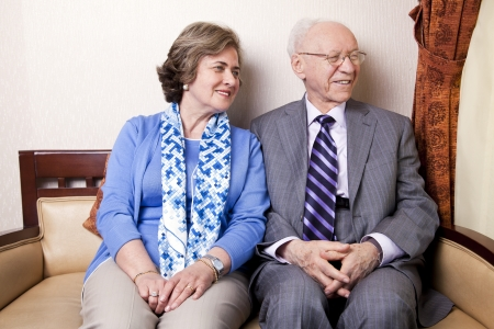 A high society senior couple (hes in his 80s, shes in her late 60s) sitting on a sofa looking away to the right side of the frame with very much love and joy. photo