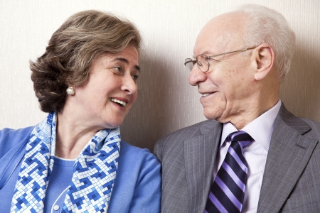 A high society senior couple (hes in his 80s, shes in her late 60s) sitting on a sofa looking at eachother with very much love and joy. photo