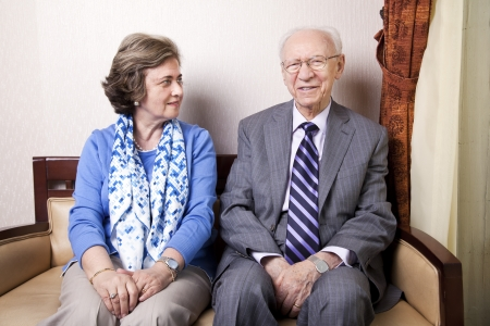 A high society senior couple (hes in his 80s, shes in her late 60s) sitting on a sofa. Shes looking away to the right side of the frame, and hes looking straight to the camera, with a slight smile on his face. photo