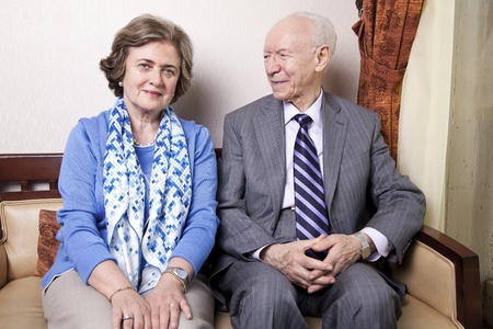 A high society senior couple (hes in his 80s, shes in her late 60s) sitting on a sofa. Hes smiling and looking at her, and shes looking straight to the camera, with a slight smile on her face. photo