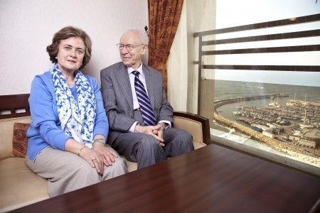 A high society senior couple (hes in his 80s, shes in her late 60s) sitting on a sofa. Hes smiling and looking at her, and shes looking straight to the camera, with a slight smile on her face. The sea and a marina can be seen in the background throu photo