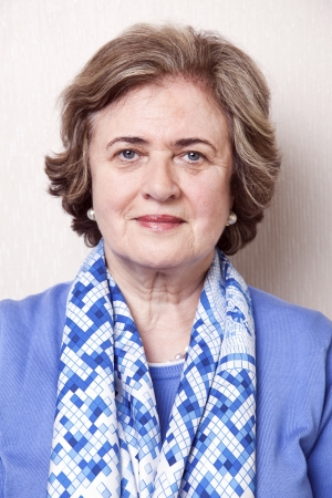 60 years old: Medium close-up portrait of an elegant amd well maintained senior woman (in her late 60s) slightly smiling to the camera. Stock Photo