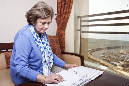 late 60s: An elderly (in her late 60s) business woman sitting in a hotels business lounge, looking down at an empty page in a dossier, holding a fancy pen just about to start writing. The sea and a marina can be seen in the background through the window. Stock Photo