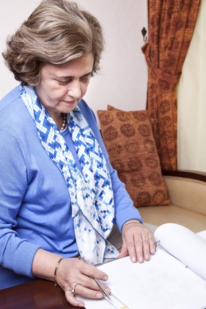 late 60s: An elderly (in her late 60s) business woman sitting in a hotels business lounge, looking down at an empty page in a dossier, holding a fancy pen just about to start writing.  Stock Photo