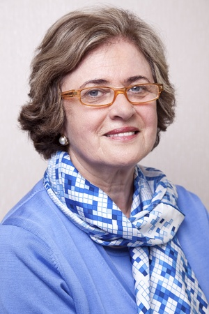 Medium close-up portrait of an elegant amd well maintained senior woman (in her late 60s) wearing glasses, smiling a toothy smile to the camera. Stock Photo