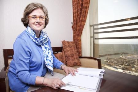 late 60s: An elderly (in her late 60s) business woman sitting in a hotels business lounge, looking at the camera, holding a fancy pen just about to start writing. The sea and a marina can be seen in the background through the window. Stock Photo