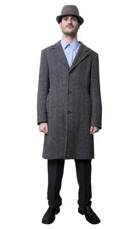maladroit: Un jeune adulte de sexe masculin portant un manteau et un chapeau assorti, en souriant et en regardant d'une mani�re maladroite � la cam�ra. Isol� sur fond blanc. Banque d'images